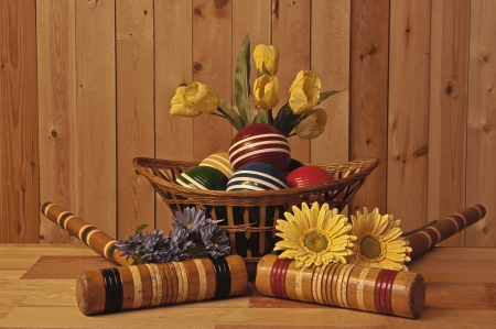 wicker basket of croquet balls mallets and spring flowers on wood background photo