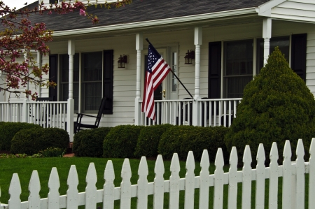 Fences: traditional white colonial home with white picket fence flying the american flag