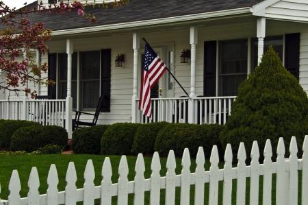 traditioneel wit koloniaal huis met witte houten schutting die de Amerikaanse vlag