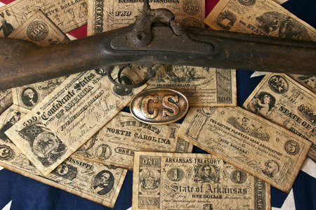 confederacy: confederate money, belt buckle, and mucket on confederate flag Stock Photo