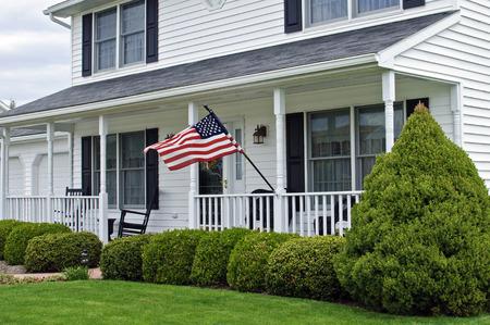 casa colonial: blanco de dos pisos casa colonial con la bandera americana Foto de archivo
