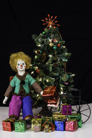 Decorated Christmas tree with lights next to doll in red rocking chair with toys and presents on white with black background  photo