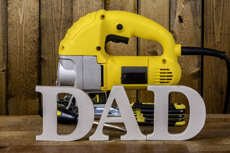 power tool: large letters spelling Dad in front of power tool