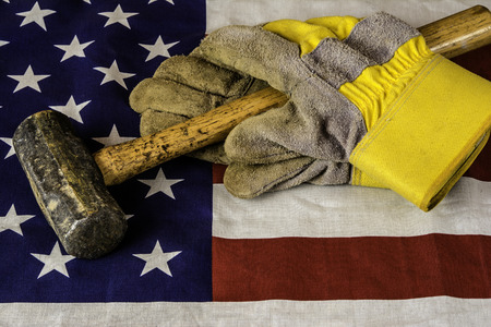 foreign trade: hammer and work gloves on american flag