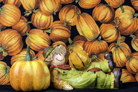 autumn scarecrow: relaxing scarecrow figurine in front of punpkins Stock Photo