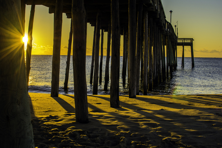 peaking: sunrise peaking through the pier supports on beach Stock Photo