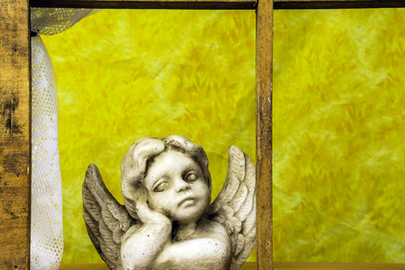 looking out: cherub looking out window with yellow background Stock Photo