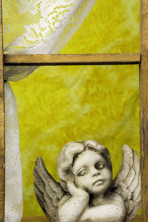 angelic: cherub statue looking out window Stock Photo
