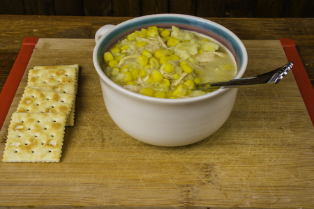 bowl of chicken corn soup and crakers