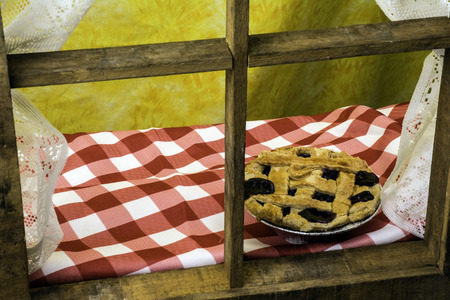 blueberry pie: blueberry pie cooling on window sill with yellow background Stock Photo