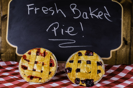 eating pastry: fruit pies on checked table cloth in front of chalkboard advertising fresh baked pies