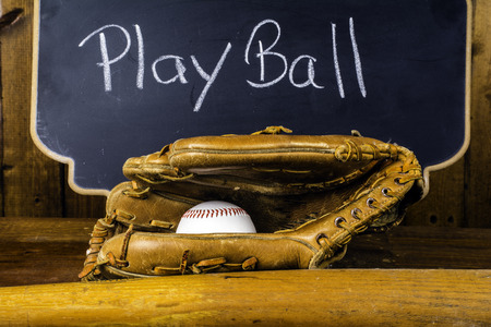 sport object: baseball equipment in front of chalkboard saying play ball