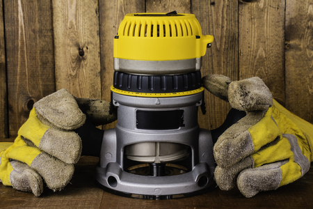 electric router and leather work gloves on wood background
