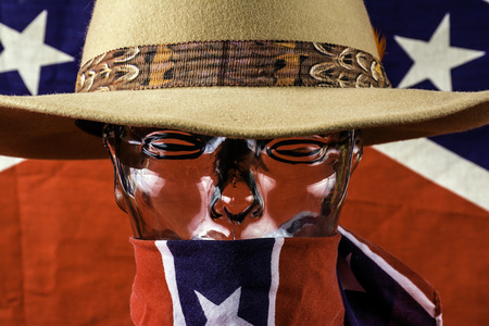to conceal: glass head wearing cowboy hat and rebel scarf Stock Photo