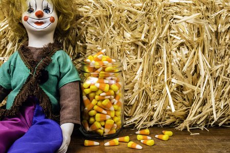 porcelain clown doll jar of candy corn and bale of straw