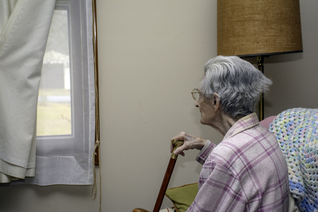 hoping: elderly woman looking out window hoping someone will visit Stock Photo