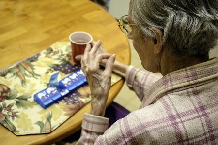 高齢者の女性が彼女の薬を服用 写真素材