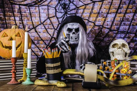 grim reaper at wood desk brick wall background with spider and web Archivio Fotografico