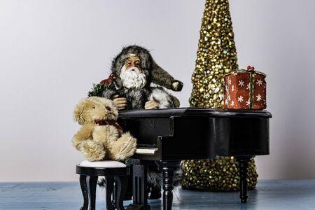 Christmas still life of Santa leaning against piano