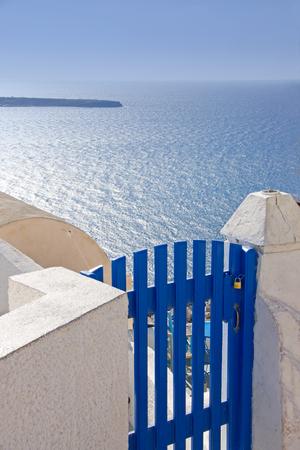 santorini greece: The blue gate in one of the houses on island Santorini, Greece overlooking the Aegean sea