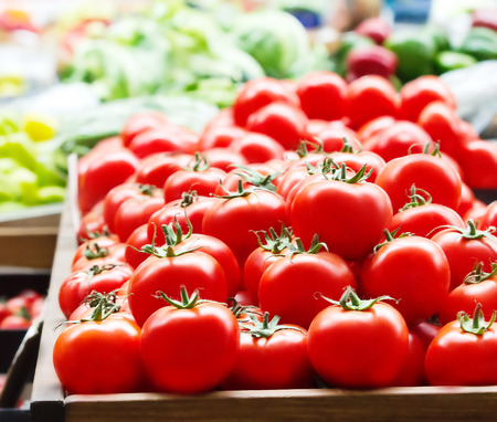 Red fresh ripe tomatoes close up and green sweet bell peppers in the background on the market