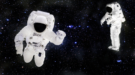 Astronauts in spacesuits floating in outer space. Spacemans at work. Starry dust.