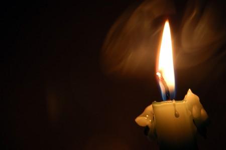 las llamas y el humo de velas, la quema en la oscuridad Foto de archivo
