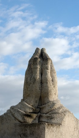 praying hands statue towards blue sky with white clouds