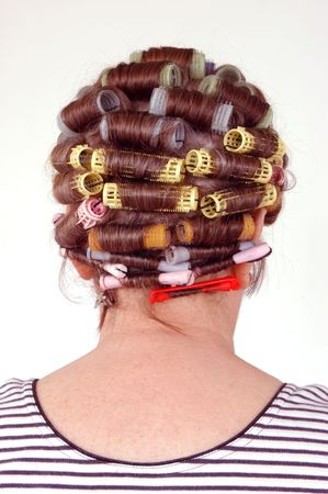 senior citizen female with hair rollers on head back view over white