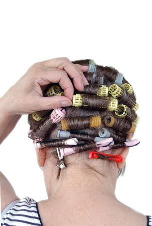 senior adjusting bobby pin and hair rollers isolated on white background photo