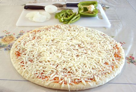 raw uncooked pizza pie with fresh cut green pepper and onion in the background as toppings