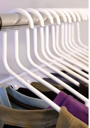 many shirts hung on white hangers