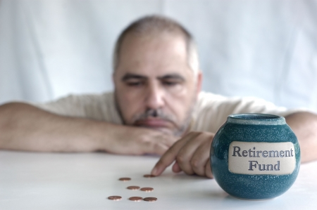 poor man: depressed man counting pennies from retirement fund