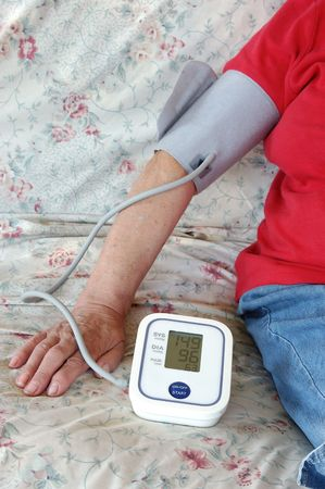 elderly woman self checking her blood pressure at home photo