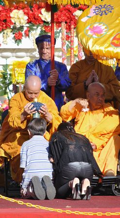 TAMPA, FL - MARCH 14: Buddhist monk blessing people with the top knot of the jade buddha statue for universal peace on display at the Minh Dang quang temple March 14, 2010 in Tampa, FL.  Editorial
