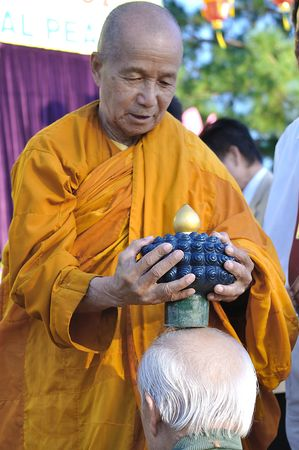 buddha image: TAMPA, FL - MARCH 14: Buddhist monk blessing people with the top knot of the jade buddha statue for universal peace on display at the Minh Dang quang temple March 14, 2010 in Tampa, FL.  Editorial