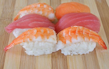 shrimp salmon and tuna sushi with white rice on bamboo cutting board Stock Photo