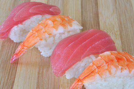 shrimp and tuna sushi on white rice on bamboo cutting board Stock Photo
