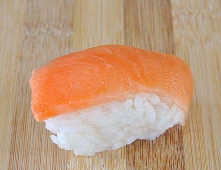 salmon sushi with white rice on bamboo cutting board