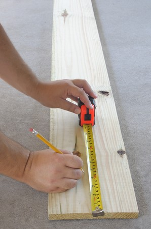 Carpentry, mans hands measuring wood board with tape measure and pencil photo