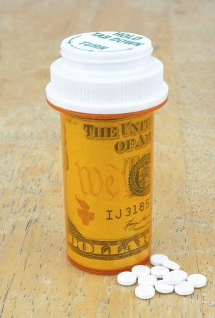 pill bottle with money Stock Photo