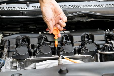 Man überprüft Öl in seinem Auto mit Ölmessstab