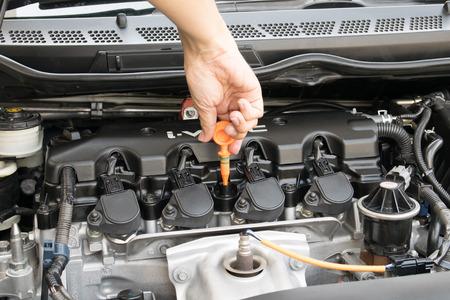 Man checking oil in his car using dipstick Standard-Bild