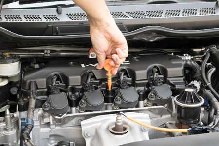 Man checking oil in his car using dipstick Imagens