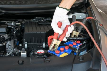 automotive technician charging vehicle battery Imagens