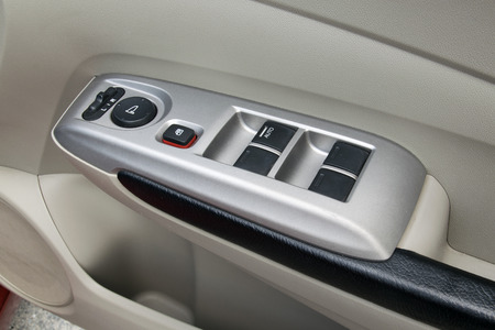 car interior details of door handle with windows controls and adjustments. Car window controls photo