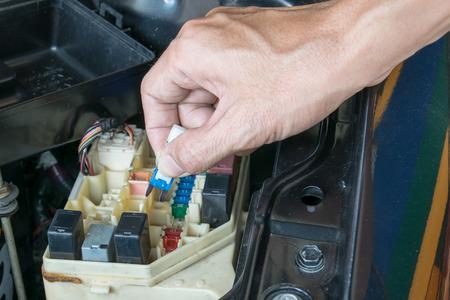 Auto mechanic checking a car fuse Banco de Imagens