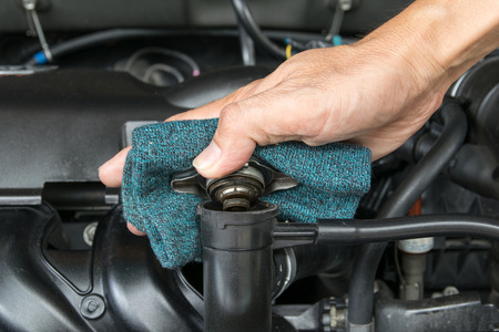 car service: hand open valve metal cover on an radiator for engine cooling