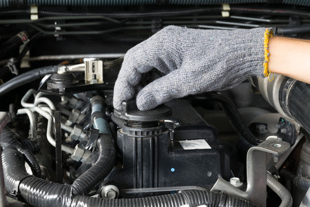 auto service: A mechanic is opening the oil cap from a car engine. Stock Photo