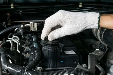 A mechanic is opening the oil cap from a car engine. Stock Photo
